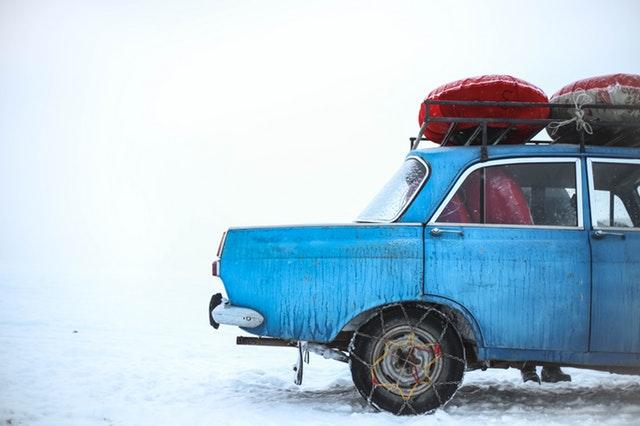 Modré auto s batožinou na streche stojí na zasneženej zemi