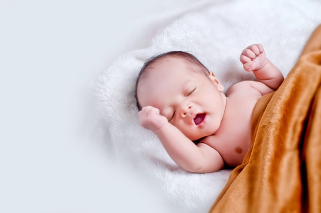 Bábätko spí na bielej kožušine zakryté oranžovou dekou.jpg