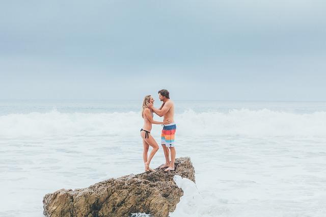 Muž drží ženu za tvár a stoja na skale v mori.jpg
