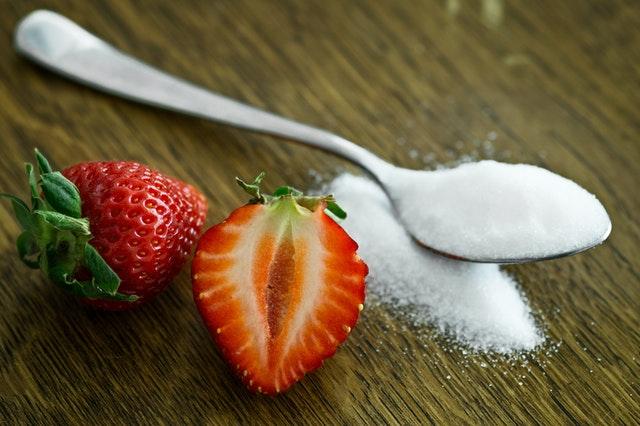 Lyžička cukru a rozrezaní jahoda