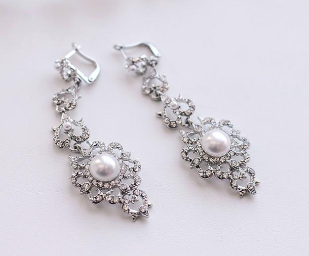 wedding-earrings-white-surface_131240-1570